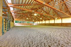 Large horse arena riding area with sand interior. Stock Photo