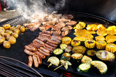 Large hot barbecue with meat, sausages and vegetables being cook Royalty Free Stock Photos