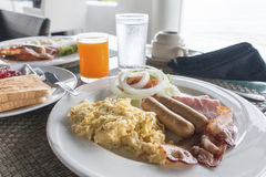 Large hot breakfast with scrambled eggs,  bacon. Sausage served with orange juice and toast `big hot breakfast Stock Image