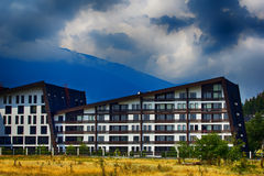 Large hotel building in the green mountain valley near forest Stock Photo