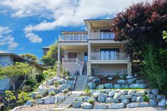 Large house with balconies on the hill with rocks. Stock Photos