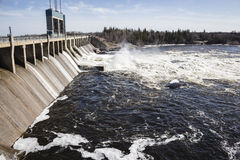 Large hydro dam with water flowing over turbines in summer time. Royalty Free Stock Images