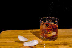 Large Ice bropped into a glass of Bourbon. Bourbon splashes as ice cubes are dropped into it Stock Photos