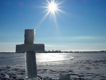 Large ice cross near the hole on the background of bright blue sky and endless frozen river stock images