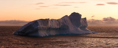 Large Iceberg Floating in Sea at Dusk Royalty Free Stock Photography