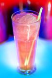 Large iced drink/cocktail. Iced pink drink with a brightly multicolored background royalty free stock photography