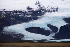 Large icelandic glacier in river shape. White Icelandic glacier in river shape on the black mountains Royalty Free Stock Photo
