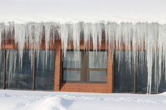 Large icicles hanging from a church roof royalty free stock images