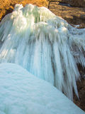 Large icicles are hanging on a rock Stock Images