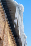 Large icicles hanging on the roof of the house Stock Photo