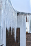 Large icicles hanging from the roof. Of the old house Royalty Free Stock Images