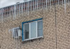 Large icicles on the roof of the building. Danger Stock Photo