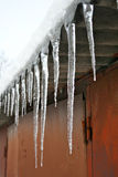 Large icicles on the roof of the garage Stock Photo