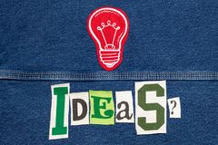 Large IDEAS- with light bulb word collage from cut out tee shirt letters on denim, brainstorming. Horizontal aspect stock photography