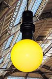 Large indoor light bulb. Large light bulb shaped light attached to the ceiling inside the restored Victorian Market Hall, Derby, Derbyshire, England, UK stock photos