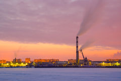 Large industrial area with big chimney at river in winter Royalty Free Stock Photo