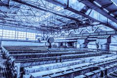 Large industrial bath for galvanizing steel metal products. Background in blue tone. Large industrial bath for galvanizing steel metal products. Hooks of Royalty Free Stock Images
