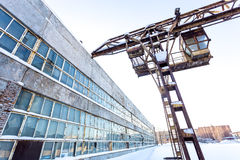 Large industrial building in abandoned factory area with rusty lift Stock Image