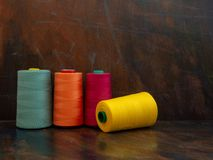 Large industrial cones of orange, teal and yellow sewing threads laying and standing on a dark background. Front view studio shot. stock photo