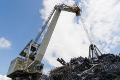 Large industrial crane and a heap of metal junk Royalty Free Stock Photography