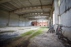 Large industrial hangar. Large industrial, military empty hangar. Mountain bikes near the wall Royalty Free Stock Photography