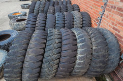 Large Tires Dozens. Large industrial heavy machinery used and new tires in yard for resale royalty free stock image