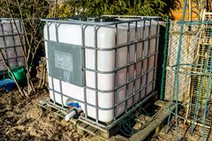 Large industrial liquid tank with a capacity of 1000 liters, 265 gallons with a metal protective grille. Placed in a home garden a. S a rainwater tank royalty free stock images