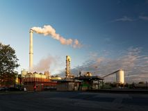 Large industrial plant at sunset. Smoke rises from a chimney Royalty Free Stock Photos