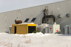 Large industrial standby generator in winter. Industrial standby generator and electrical service with solar panels Royalty Free Stock Photography
