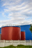 Large industrial tanks of red color against the blue industrial building royalty free stock images
