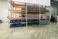 Long shelves with a variety of boxes and containers. Large industrial warehouse. Long shelves with a variety of boxes and containers Stock Photography