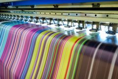 Large inkjet printer working multicolor on vinyl banner. Large inkjet printer working multicolor cmyk on vinyl banner Royalty Free Stock Photo