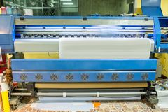 Large inkjet printer working on sticker paper. In factory stock photo