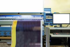 Large inkjet printer working on vinyl banner with computer. Control stock images