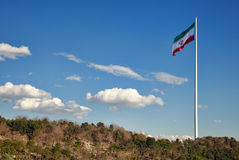 Large Iran Flag Waving in the Wind against Cloudy Blue Sky above Green Park Area in Tehran royalty free stock image