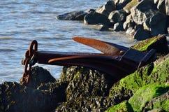 Large iron anchor on rocks Royalty Free Stock Photo