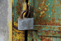 Large iron lock on an old door. Large iron padlock on a background of an old door Royalty Free Stock Images