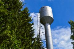 Large iron metal shiny stainless industrial water tower for supplying water with a large capacity, barrel against the blue sky. And trees stock image