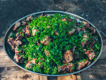On a large iron plate lined with diced, roasted on the grill pork meat and sprinkled with dill and parsley. Stock Photos