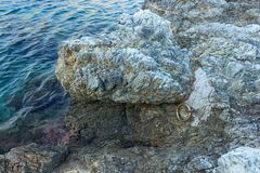 Large iron ring in the rock for mooring boat. Calm sea. Greece. Large iron ring in the rock for mooring boat. Calm sea Royalty Free Stock Photography