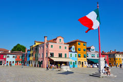 Large Italian flag fly above Burano island piazza square Stock Images