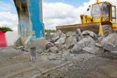 Large jackhammer crushing asphalt paving during road works. Large jackhammer crushing asphalt paving during road construction works and wheel loader moving break royalty free stock photo