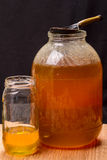 Large jar with honey and wooden spoon Royalty Free Stock Images