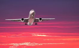 Large jet arriving at sunset. Widebody airliner on approach with colorful dramatic sky in the background Stock Photo