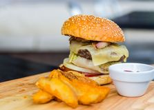 Large juicy burger with a delicious beef patlet with fried potato slices, a quick lunch Stock Image