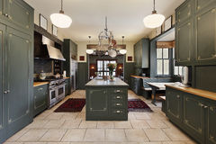 Large kitchen with green cabinetry Royalty Free Stock Photo