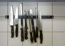Large kitchen knives and honing steels hanging on a magnetic holder on the tiled wall, copy space. Large kitchen knives of stainless steel and honing steels royalty free stock image