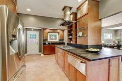 Large kitchen room interior with brown cabinets and steel appliances Royalty Free Stock Photos