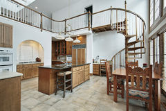 Large kitchen with spiral stairway to second floor Royalty Free Stock Photos