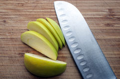 Large knife and apple on a wooden board Stock Photo